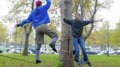 Laura Lantz and Andrew Dekkinga of Slackline Pittsburgh high-five each other as they walk on the slackline ropes.