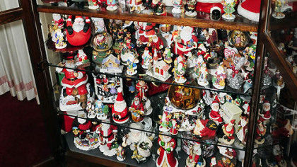 The display case in Carol Vicini's home showcases about 400 Santa figures from around the world. Some were made by Lennox and Goebel.