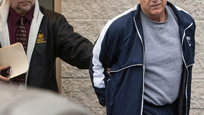 Former Penn State assistant football coach Jerry Sandusky, right, leaves the office of Centre County District Justice Daniel A. Hoffman on Wednesday under escort by Pennsylvania State Police and Attorney General&#039;s Office officials in Bellefonte.