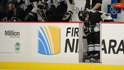 Sidney Crosby bends over in pain on the bench in the third period Monday after colliding with teammate Chris Kunitz. Crosby returned to the game against the Bruins, but was given a maintenance day at practice Tuesday. He is expected to practice today.