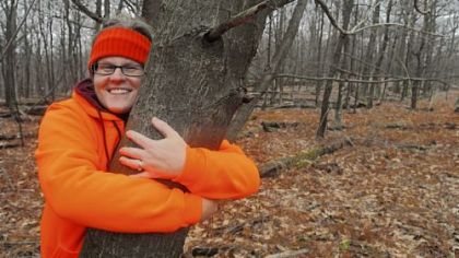 Sara Fitzsimmons hugs an American chestnut tree found growing in the wild near the orchard she helped plant. This tree is about 40 feet tall and is producing nuts but shows signs of chestnut blight.