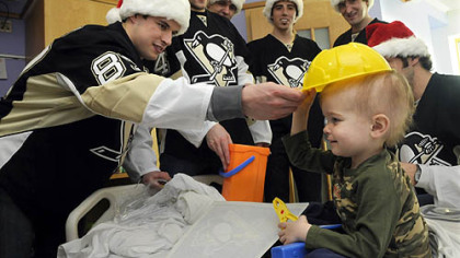 Penguins player Sidney Crosby places a toy hard hat on Camden Lookabaugh, 3, of New Kensington during a visit to Children's Hopsital of Pittsburgh of UPMC in Lawrenceville. Camden received a toy tool box from the players.