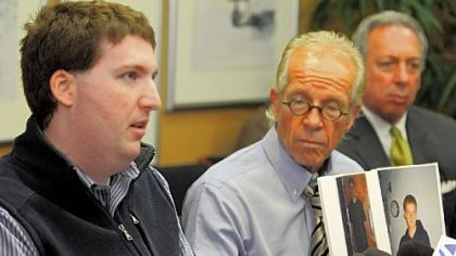 Zachary R. Tomaselli, left, reads a statement regarding his civil suit against Bernard Fine as he speaks to reporters with his lawyers, Jeff Anderson and Alan H. Perer.