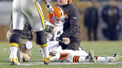 Browns quarterback Colt McCoy gets attention after receiving a hit from the Steelers' James Harrison.