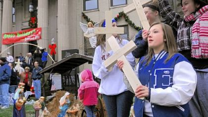 Morgan Prokovich, right, 17, holds a wooden cross at a community demonstration Friday in favor of Ellwood City?s creche displayed on the lawn of the municipal building.