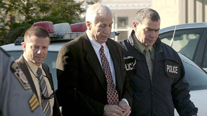 "Former Penn State football defensive coordinator Gerald ""Jerry"" Sandusky, center, walks to the office of Centre County Magisterial District Judge Leslie A. Dutchcot on Nov. 5 in State College escorted by Pennsylvania State Police and Attorney General's Office officials."