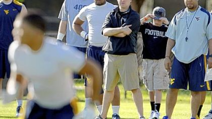 West Virginia coach Dana Holgorsen, center, watches practice Friday at Barry University in Miami Shores, Fla.