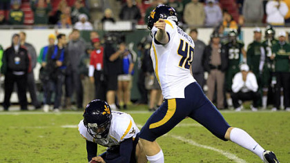 West Virginia's Michael Molinari, left, holds as kicker Tyler Bitancurt (40) winds up to attempt a game-winning field goal as time expires against South Florida last night in Tampa.