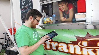 Dave White completes his order with one of Franktuary's owners, Megan Lindsay, at the Franktuary truck parked behind 2700 Jane St. on the South Side.