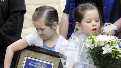 The daughters of slain officer Stephen Mayhle -- Jennifer, 8, left, and Brooklynn, 5, clutch a plaque and flowers presented to the families of Mayhle, Eric Kelly and Paul Sciullo II following the dedication of a sculpture of St. Michael.