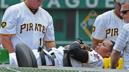 Pirates manager Clint Hurdle helps injured player Jose Tabata onto a stretcher.