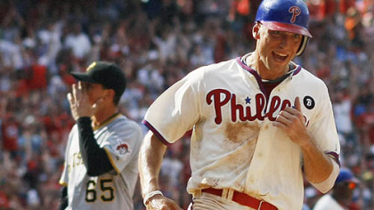 Phillies' Hunter Pence, right, scores the winning run as Pirates relief pitcher Tony Watson, left, walks off the field in the 10th inning of a baseball game.