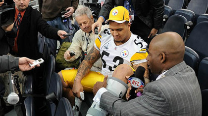 Steelers center Maurkice Pouncey  shows NFL Network&#039;s Deion Sanders his injured left ankle during Super Bowl XLV Media Day at Cowboys Stadium in Arlington, Texas Tuesday.