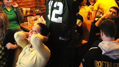 Green By fan Ed Pajewonsky of Stroughsburg, Pa., puts his hands in the air after the Steelers' final fourth down as Danielle Prima of Oakland watches in disbelief at Piper's Pub in Oakland.
