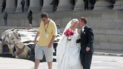 "WPXI sports anchor Rich Walsh and his bride, Michele, share a kiss after getting a close look at the Batmobile (also known at The Tumbler) on the set of ""The Dark Knight Rises"" on Fifth Avenue in Oakland. Mr. and Mrs. Walsh had just finished their wedding ceremony at St. Paul Cathedral."