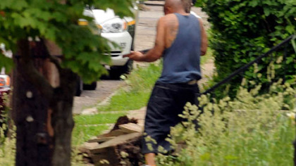 A man emerges from a house in Larimer, armed with a shotgun. He was shot by police after they ordered him to drop his weapon.