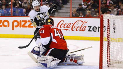 Penguins forward Tyler Kennedy redirects a point shot into the net in behind Senators goaltender Craig Anderson during the first period of tonight's game at Scotiabank Place in Ottawa