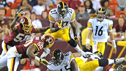 Pittsburgh Steelers Jonathan Dwyer leaps over the Redskins defense picking up a first down in the fourth quarter of Friday&#039;s game.