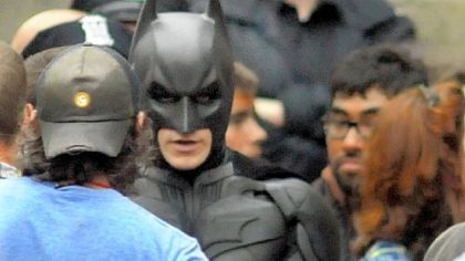"""Batman"" speaks with production crew before filming a fight scene for ""The Dark Knight Rises"" in Oakland."