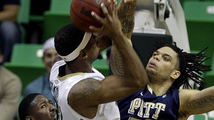 Pitt center Gary McGhee blocks a shot by South Florida center Jarrid Famous during the first half of Wednesday's game in Tampa, Fla.