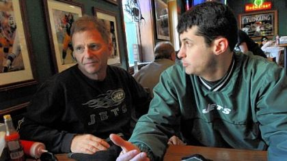 Howard Fuchs, left, of Sarasota, Fla. (formerly of the Bronx), and his son. Jason Fuchs of Petoskey, Mich., eat lunch at Primanti Brothers restaurant in Market Square, Downtown. The Jets fans are in Pittsburgh for the AFC Championship today. On the wall behind them are photos of the Steelers.