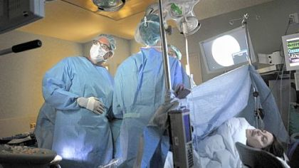 Dr. Stephen Emery, fetal surgeon, left, prepares to have the laser activated by the operating room team for surgery done to the placenta of Rachel Lendyak-Peters, right, which is being shared by her identical twins.