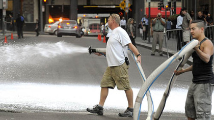 Fake snow is sprayed on Oliver Avenue at William Penn Place before filming begins in Downtown Pittsburgh Aug. 10.