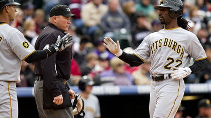 Andrew McCutchen is welcomed home by Ronny Cedeno after Garrett Jones' two-run single Sunday.