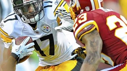 Wide receiver Mike Wallace attempts to fend off the tackle of Redskins cornerback DeAngelo Hall in the first quarter Friday night at FedEX Field.