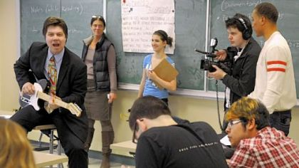 Pittsburgh CAPA student David Becinski shoots video of 12th-grade English teacher Jim Addlespurger playing guitar and singing as he teaches Shakespeare and The Blues. Viacom&#039;s Tony Anderson, right, looks over David&#039;s shot. CAPA students are making a video about their school as part of a competition to have President Barack Obama as their commencement speaker.