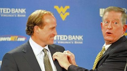 Dana Holgorsen, left, new West Virginia's football offensive coordinator and quarterbacks coach receives a West Virginia pin from head coach Bill Stewart at a press conference in Morgantown, W. Va Dec. 22, 2010.