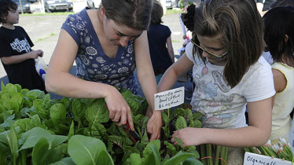 Farmer Gillian Goldberg, left, helps Zoe Moran, 11, of Arlington, pick out a Swiss chard plant at the Who Cooks for You Farm stand on the opening day of the CitiParks Farmers&#039; Market in East Liberty.
