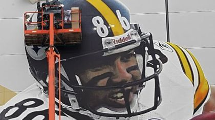 Workers put up a picture of Steelers receiver Hines Ward outside Cowboys Stadium in preparation for Super Bowl XLV Sunday in Arlington, Texas.