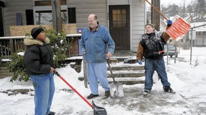 Derrick Smith, 13, left, and Benjamin Payne, 14, right, shovel snow outside the home of Jeff Owen, center, in Pitcairn. Mr. Owen is rehabbing the house and downsizing to Pitcairn from a home in Murrysville.