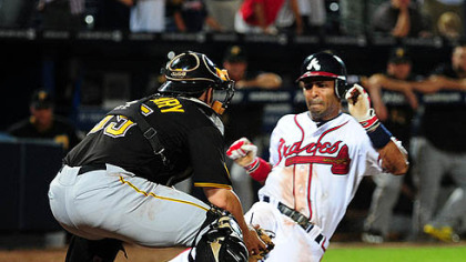 The Braves' Julio Lugo scores the game-winning run in the 19th inning against Pirates catcher Mike McKenry at Turner Field in Atlanta Tuesday. McKenry appeared to make the tag before Lugo touched the plate but umpire Jerry Meals called him safe.