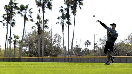 Pirates non-roster player Eric Fryer throws at a voluntary spring training workout Sunday in Bradenton, Fla. Pitchers and catchers begin workouts today.