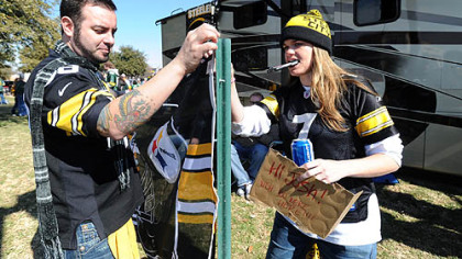 Steelers fans Chris Kirkpatrick of Orlando, Fla., formerly of Clarion, and Katy Dierks of Los Angeles, hang a Steelers flag outside the RV they drove with friends from Orlando to Texas to see the game.
