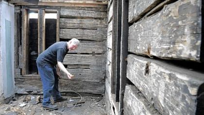 Lawrenceville architect Keith Cochran pulls a peg from one of the large logs in the home at Charlotte and 38th streets in Lawrenceville, below. The 1822 log home may be torn down, but the logs could be saved and cataloged until they can be reassembled somewhere else in Lawrenceville.