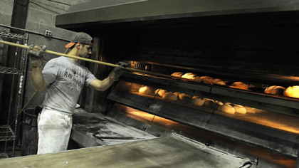 Mike Ambeliotis works the oven at the Mediterra Bakehouse in Robinson.