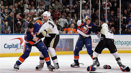 Islanders defenseman Travis Hamonic fights Penguins forward Michael Rupp (right) as Islanders forward Josh Bailey battles Penguins forward Pascal Dupuis during the second period of a game Feb 11, 2011 at Nassau Coliseum in Uniondale, New York. The teams meet again tonight.