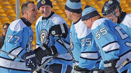 From left to right, Penguins alumni Paul Coffey, Mario Lemieux, Kevin Stevens and Larry Murphy celebrate a goal against during Friday's game at Heinz Field.