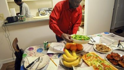 Ismail Omar, foreground, prepares for dinner with Mohamed Idris.