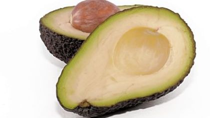 Avocado cut in half, with its stone/seed exposed.