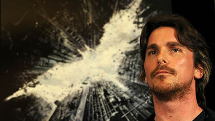 "Actor Christian Bale listens to director Christopher Nolan and others at a press conference for ""The Dark Knight Rises"" at the Renaissance Hotel, Downtown."