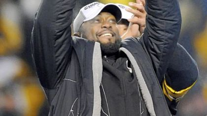 Steelers coach Mike Tomlin hoists of the trophy after defeating the Jets at AFC Championship at Heinz Field Sunday.