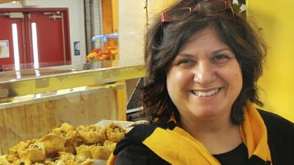 Zelfa Khalil of The Baklava Company at the Pittsburgh Public Market shows a tray of filo footballs decorated in a black and gold theme for the Super Bowl.