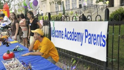 Muzz Meyers from Communities in Schools sits at the welcome table to talk with parents outside the Academy at Westinghouse.