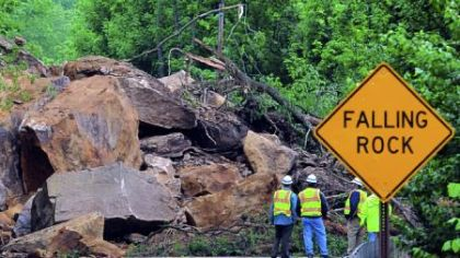 PennDOT officials are dwarfed by the boulders that landed on Route 88 in East Bethlehem, Washington County. PennDOT District 12 executive  Joe Szczur said rock is still hanging about 80 feet above the road.
