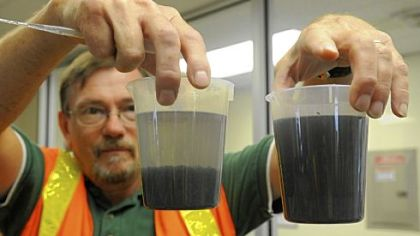 Kevin Warheit, a product manager with Siemens, holds two samples of flowback water. The water on the left has been treated with a polymer and coagulant to make the particles form a sludge. The sludge is then put into a filter press and made into a nontoxic cake that can be disposed of.