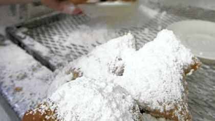 A waitress puts powdered suger on plates of beignets at Cafe Du Monde.